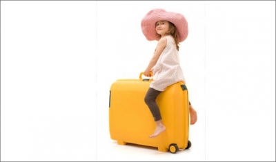 kid sitting on luggage 0